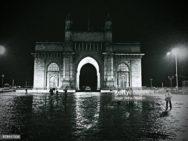 People At Gateway To India In City At Night
