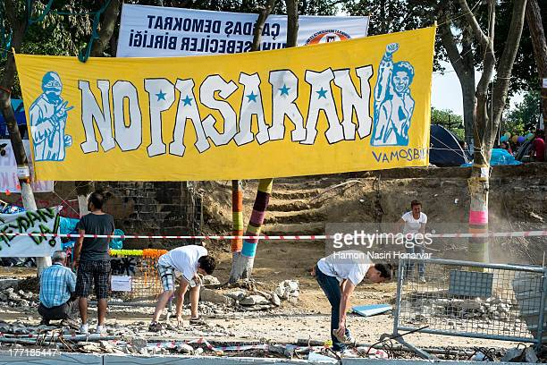 People at Gezi Park cleaning the area. No pasaran poster is hanged between trees.