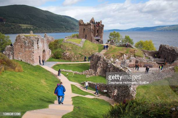 people at historic ruined building by sea against sky - loch ness stock pictures, royalty-free photos & images