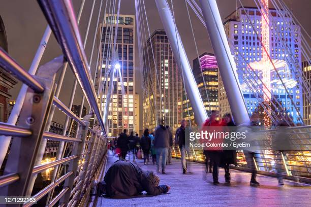 people at illuminated city at night - crisis stock pictures, royalty-free photos & images