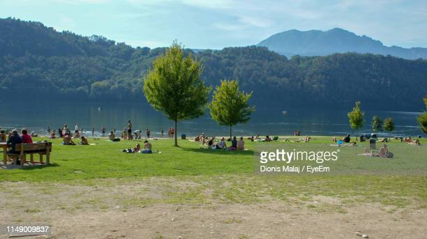 people at lakeshore against mountains - lakeshore stock pictures, royalty-free photos & images
