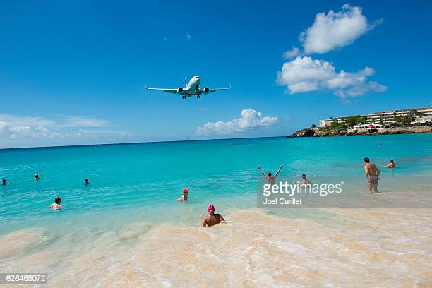 People at Maho Beach St. Maarten watching airplane land