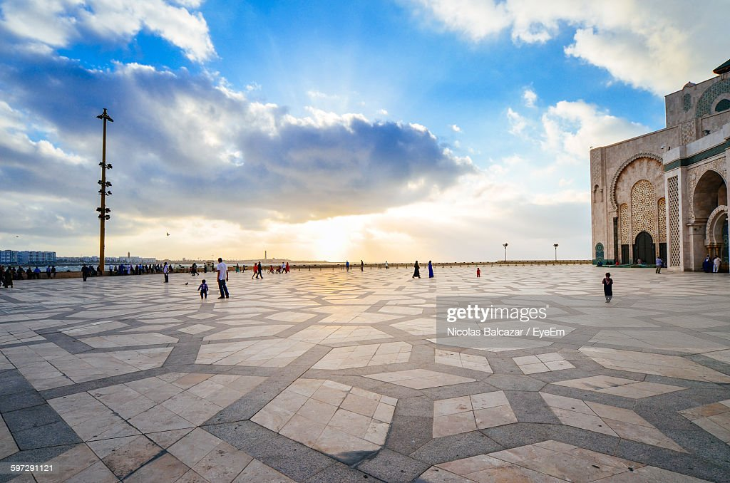 People At Mosque Hassan Ii Against Sky In City : Stock Photo