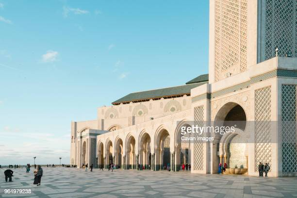 people at mosque hassan ii against sky - mosque hassan ii stock photos and pictures