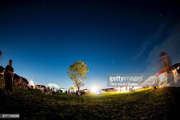 people at music concert on field against sky during night - entertainment event stock pictures, royalty-free photos & images
