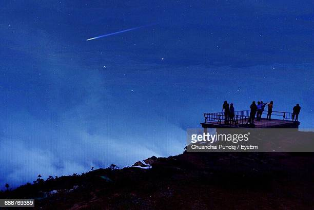 People At Observation Point On Mountain Against Blue Sky At Night