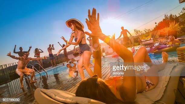 partido de la gente en la piscina bailando y saltando en la piscina al atardecer - pool party fotografías e imágenes de stock