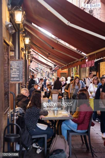 people at restaurants in the street market of bologna, italy. - bologna stock pictures, royalty-free photos & images