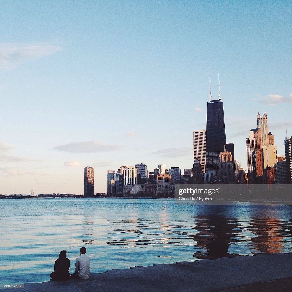 People At Sea Shore By Modern City Against Sky : Stock Photo