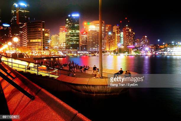 People At Sydney Harbour Bridge In Illuminated City By Sea At Night