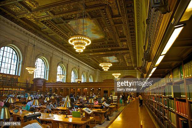 People at tables near books in huge reading room