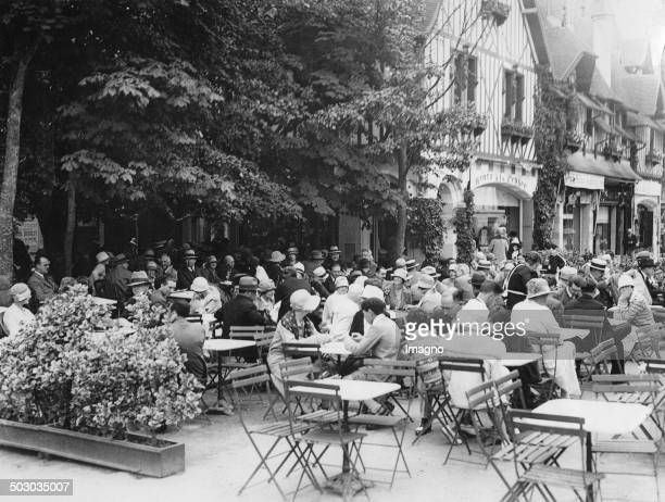 People at the aperitif in Deauville / France. About 1935. Photograph.