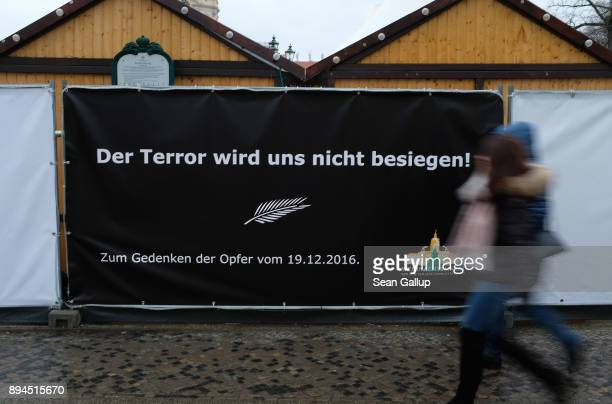 People at the Christmas market at Schloss Charlottenburg palace walk past a black billboard that reads 'Terror will not conquer us In commemoration...