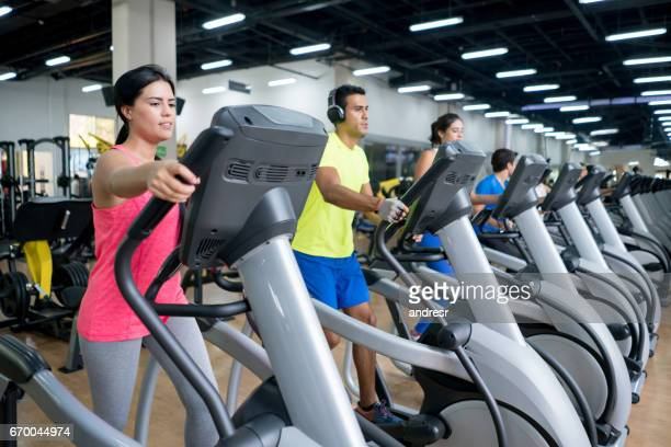 People at the gym exercising on crosstrainers