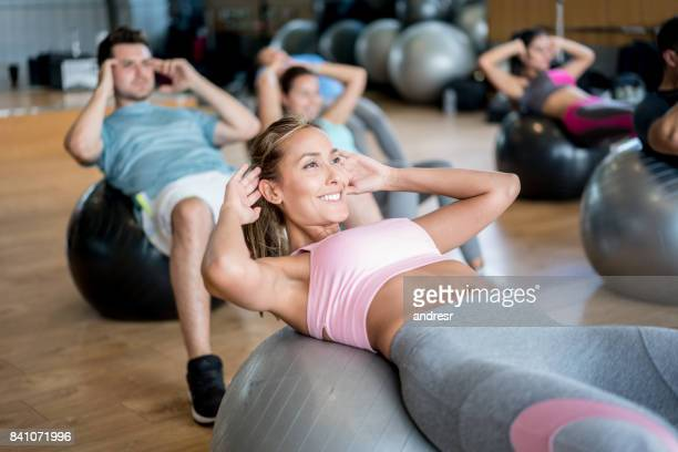 people at the gym in an exercise class using fitness balls - pilates foto e immagini stock