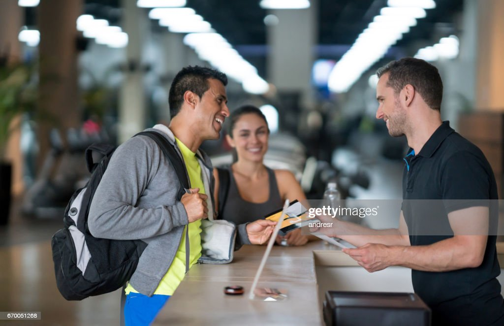 People at the gym talking to the receptionist : Stock Photo