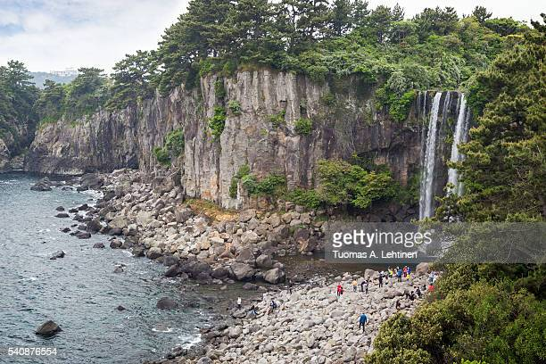 people at the jeonbang waterfall on jeju island in south korea. - jeju stock photos and pictures