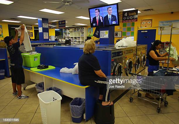People at the Lavanderia coin laundry watch as US President Barack Obama and Republican presidential candidate and former Massachusetts Governor Mitt...