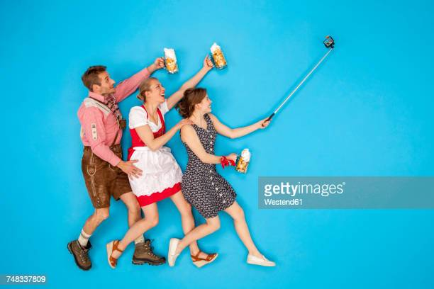 People at the Okoberfest taking selfies with beer mugs in their hands