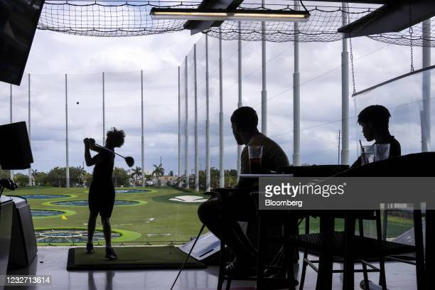 People at the Top Golf driving range in the Miami Gardens neighborhood of Miami, Florida, U.S., on Monday, April 12, 2021. The U.S. Economy is on a...