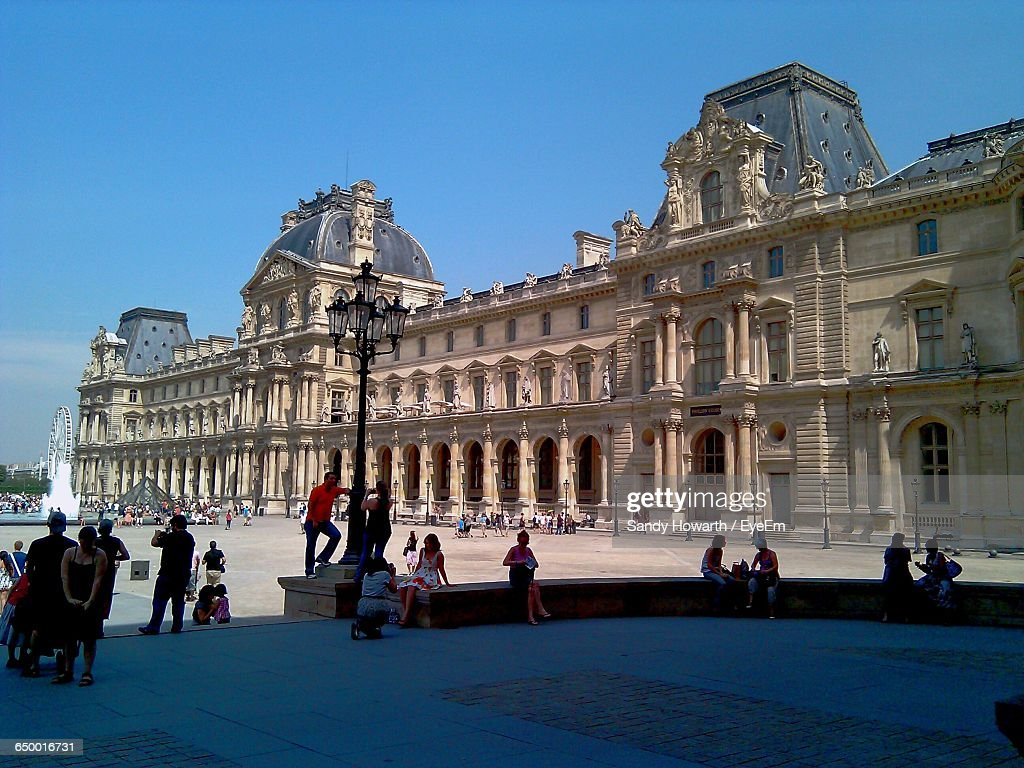 People At Town Square By Musee Du Louvre Against Sky : Stock Photo