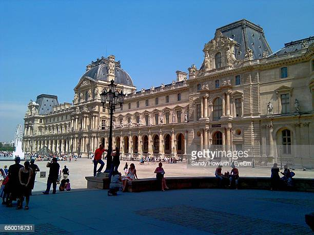 people at town square by musee du louvre against sky - louvre photos et images de collection