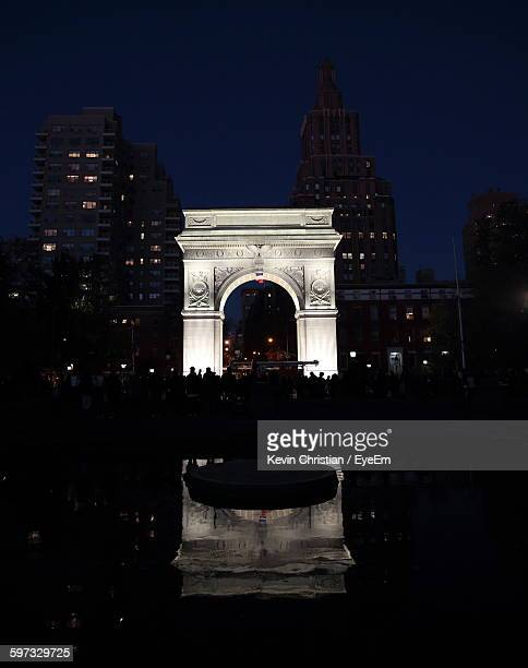 people at washington square park in city against sky at night - washington square park stock pictures, royalty-free photos & images