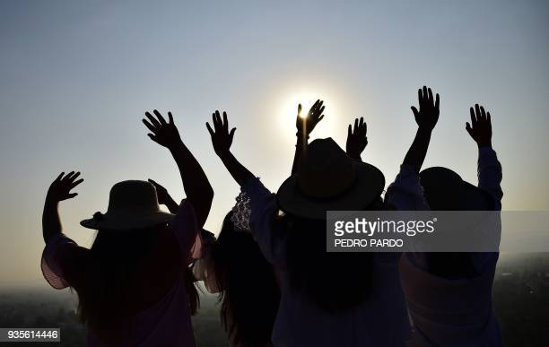 People atop the Pyramid of the Sun at the archaeological site of Teotihuacan in the municipality of Teotihuacan northeast of Mexico City get energy...