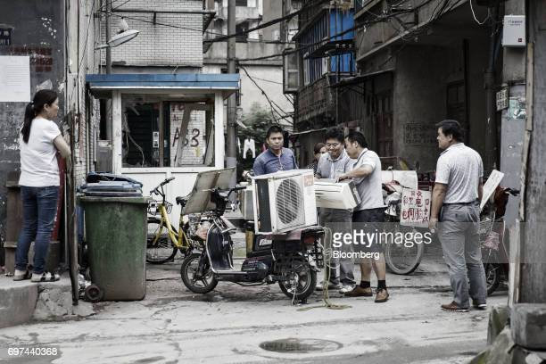 People attach an air conditioners onto a scooter in Wuhan China on Wednesday June 14 2017 China's central bank boosted the supply of cash in the...