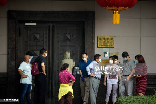People attempt to talk to someone at the Chinese consulate in Houston on July 22, 2020. - US-Chinese tensions, already rising because of the...