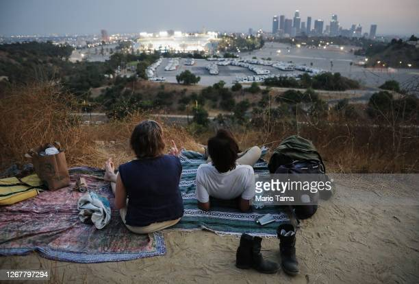People attempt to watch a game between the Colorado Rockies and the Los Angeles Dodgers from a hillside overlooking Dodger Stadium, while listening...