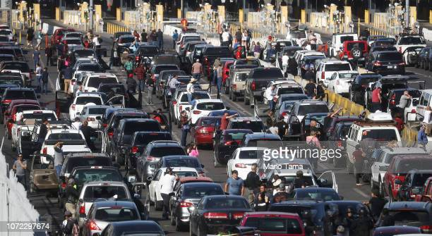 People attempting to cross into the US look on by their vehicles as the San Ysidro port of entry stands closed at the USMexico border on November 25...