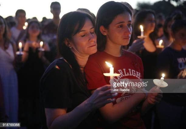 People attend a candlelight memorial service for the victims of the shooting at Marjory Stoneman Douglas High School that killed 17 people on...