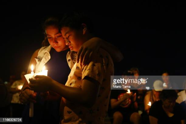 People attend a candlelight prayer vigil outside Immanuel Baptist Church, located near the scene of a mass shooting which left at least 22 people...