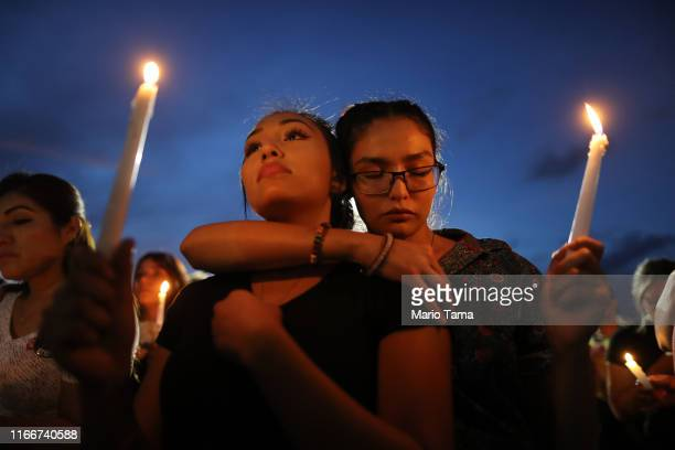 People attend a candlelight vigil at a makeshift memorial honoring victims of a mass shooting which left at least 22 people dead on August 7 2019 in...