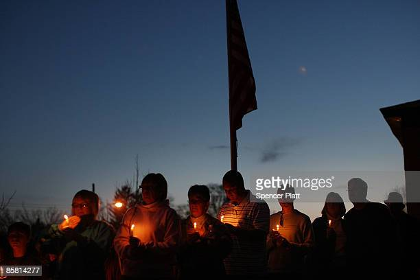 People attend a candlelight vigil following an interfaith memorial service at West Middle School in Binghamton following a recent mass shooting in...