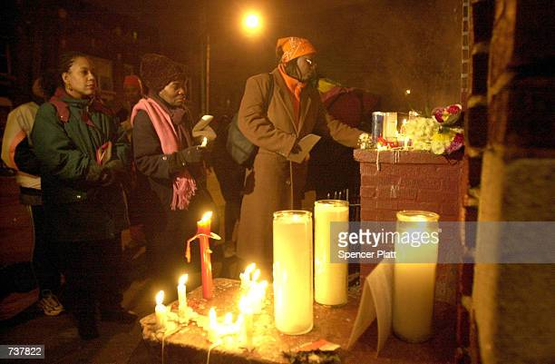 People attend a candlelight vigil for Amadou Diallo February 4 2001 in the Bronx borough of New York City beside the doorway where the West African...