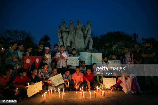 People attend a candlelight vigil for the victims of the USBangla plane crash on March 13 2018 in Dhaka Bangladesh At least 50 people were killed on...