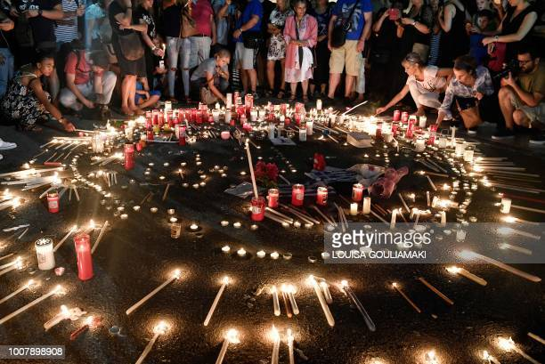TOPSHOT People attend a candlelight vigil in front of the Greek parliament in Athens on July 30 to commemorate victims of the country's worst ever...