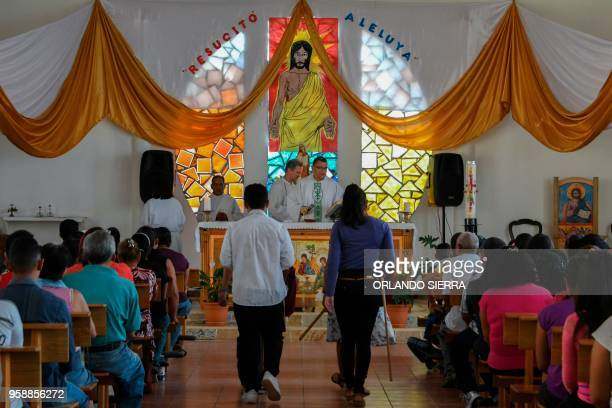 People attend a Catholic church where authorities provide assistance to exgang members in the poor neighbourhood of Nueva Capital on the outskirts of...