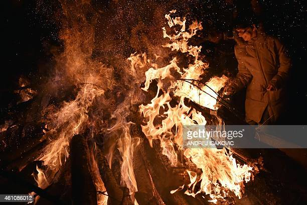 People attend a ceremonial burning of dried oak branches the Yule log symbol for the Orthodox Christmas Eve in front of a church in Smederevo 60...