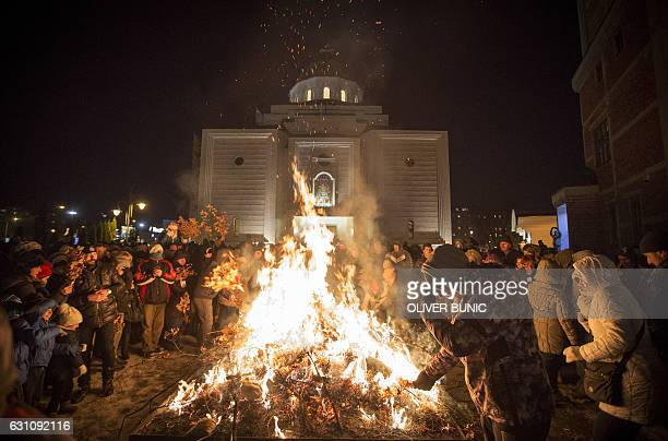 People attend a ceremonial burning of dried oak branches the Yule log symbol for the Orthodox Christmas Eve in front of Saint Demetrios church in...