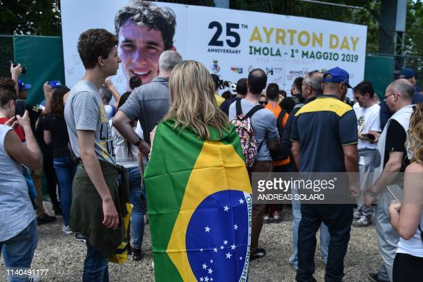 People attend a ceremony on May 1 2019 marking the 25th anniversary of the death of Brazilian's F1 driver Ayrton Senna on the Tamburello track of the...