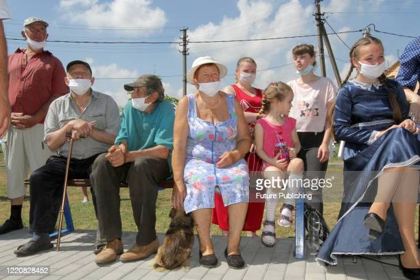 People attend a ceremony where 13 families from temporarily occupied areas of Donetsk and Luhansk Regions are set to receive the keys to apartments...