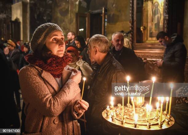 People attend a Christmas Mass at the Sioni cathedral in Tbilisi late on January 6 2018 Orthodox Christians celebrate Christmas on January 7 in the...