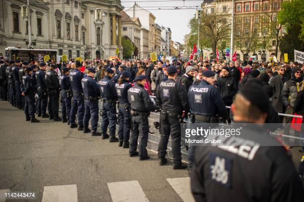 People attend a demonstration against Austria's Identarian movement as police officers stand guard during an Identitarian protest in front of the...