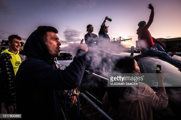 People attend a drive-in hip hop concert of Kontrafakt band on June 05, 2020 at a car race track Slovakia ring in Orechova Poton, some 45 kilometers...