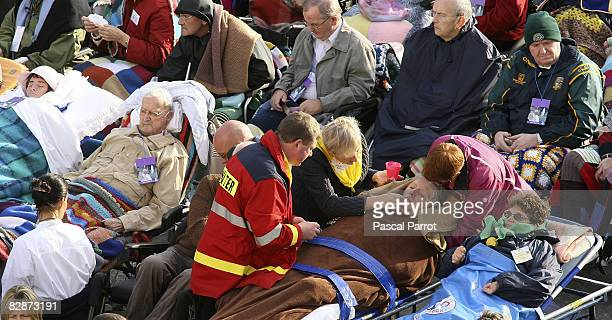 People attend a holy mass for the sick and disabled celebrated by Pope Benedict XVI in front of the Rosary Basilica September 15 2008 in Lourdes...