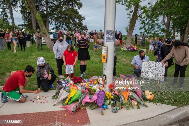 People attend a memorial at the location where a family of five was hit by a driver, in London, Ontario, Canada, June 7, 2021. Four of the members of...