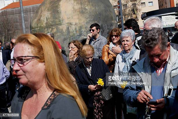 People attend a memorial gathering for the victims of Madrid train bombings outside Atocha railway station on the 10th anniversary of the attack on...